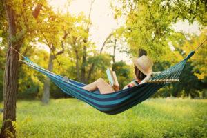 Vrouw leest boek in hangmat in tuin