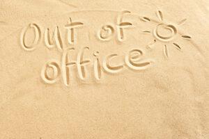 Out of office geschreven in het zand